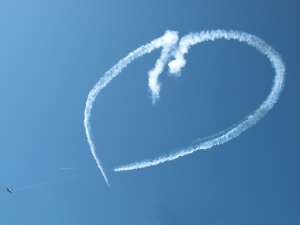 Photo of  heart-shaped contrails in sky made by stunt planes.