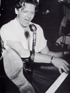 Jerry Lee Lewis with shoe on piano, black and white shot