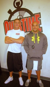 Matt Larkin and Jorge Aguirre, certified fitness trainers, post in front of Overtime Fitness gym wall logo
